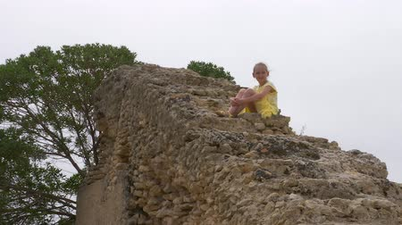 archeologie : Teenager girl sitting on top famous rocky stairs in ruined Carthage in Tunisia