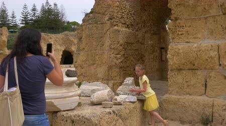 equilibrium : Young mother doing photo on mobile phone to daughter in ruined Carthage Tunisia Stock Footage