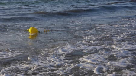 фехтование : Yellow buoy floating on shallow in sea with waves, 120fps slow motion concept Стоковые видеозаписи