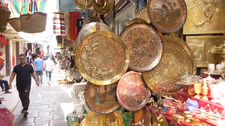 arabian : Tunis, Tunisia - 06 June 2018: Arabian market souvenirs and utensils from gold brass. Tourists walking in local market of arabian cloth and dishes.