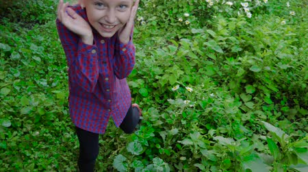 kamilla : Young girl in fear and afraid while going through green bushes and trees thicket with chamomile flowers