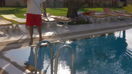 служба : Hotel worker cleaning water in swimming pool, cropped view Стоковые видеозаписи