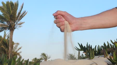 ostříhané : Male hand poured out sand on wind as time passing in desert. Time spent concept
