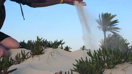 tunisia : Man with sand in palms blowing it on wind and cleaning hands