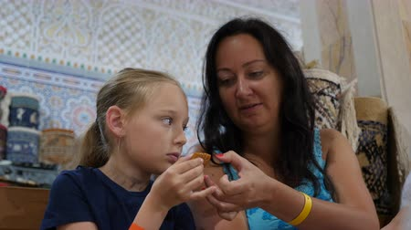 кусок : Mom and daughter eating eastern sweets at confectionery store close up