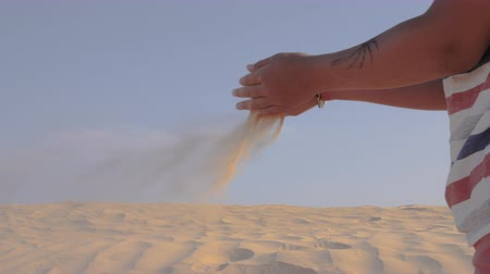 gevşek : Sand is pouring through the childs fingers in the wind. Time concept