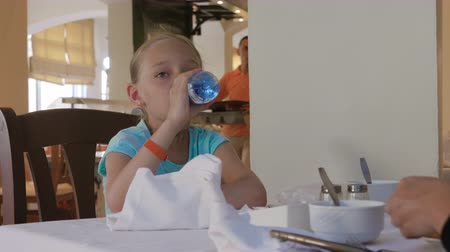 restaurante : Young girl drinking water from bottle at table in restaurant