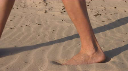 следы : Close-up of male feet sink in the sand. Walk barefoot in the desert. The man is walking past the camera, the feet sink in the sand. Hot sand. Walk in the desert