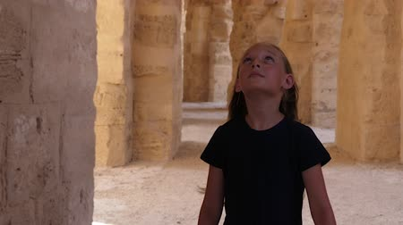 tunisia : Walking girl looking up and around on corridor with arches and columns beige color Stock Footage