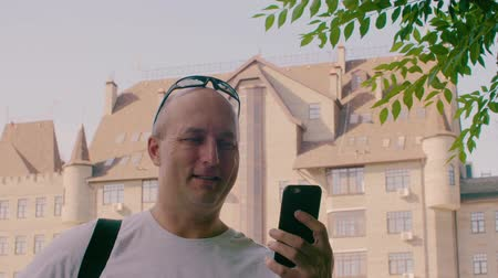 do widzenia : Happy man waving and talking on facetime with smartphone in city on sunny day. Video call, talking via internet, video chatting on smart phone. Waving goodbye communication Wideo