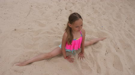 jimnastik : Young girl doing splits and stretching on sandy beach, overhead view