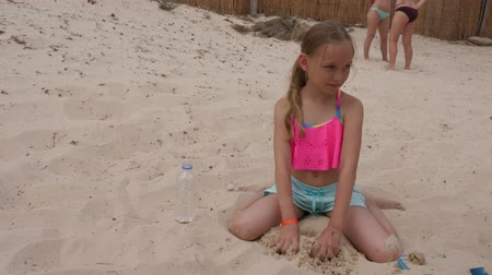 meninas : Adorable female child playing with sand and sitting on beach