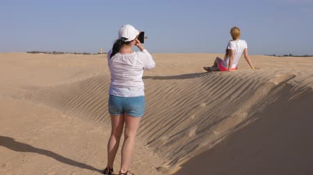 tunisia : Douz, Tunisia - 10 June 2018: young woman making photo by mobile phone while tourist excursion in Sahara desert. Tourist people photographing on dunes in sandy desert.