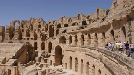 посещающий : El Jem, Tunisia - 10 June 2018: group of tourists visiting antique amphitheater Gordian while historic excursion. Tourist walking in old amphitheatre. Стоковые видеозаписи