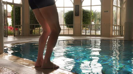 refresh : Man jumping and diving with splash in indoor swimming pool
