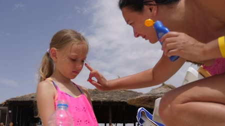 ailelerin : Young mother applying sunscreen lotion on face skin to daughter on beach
