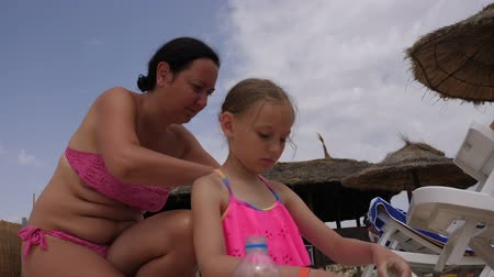 applying : Young mother applying sunscreen cream on body to daughter on summer beach