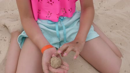 bolas : Teenager girl making sandy balls while play on summer beach close up