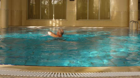łysy : Bald man swimming front crawl in indoor pool, back view, slow motion