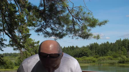 asa : Dragonfly flying over head of bald man on background summer nature and pond Stock Footage
