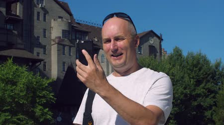 łysy : Bald man using mobile phone for video call and waving hand outdoor Wideo
