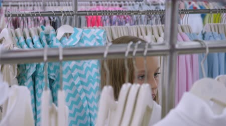выбирать : Young blonde girl choosing fashionable clothes in boutique