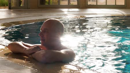 nyaraló : Portrait adult man relaxing in swimming pool near edge in luxury hotel