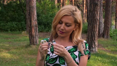 kamilla : Portrait blonde woman guessing on white chamomile in summer forest