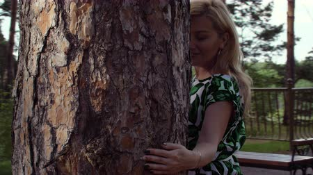 kamilla : Attractive woman walking around pine tree trunk in summer park