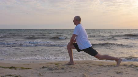 pozisyon : Athlete man doing stretching exercise to leg on sea shore, water waves background Stok Video