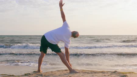 pozisyon : Adult man practising yoga pose on sea beach. Yoga training on empty beach