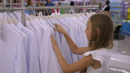 выбирать : Teenager girl choosing white blouse in clothing store. Fashion and shopping