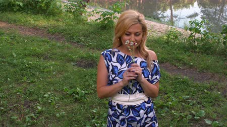 kamilla : Smiling woman sniffing fragrance of chamomile flowers and looking to sky