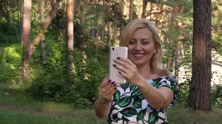 conferência : Beautiful smiling woman having video chat with phone in park