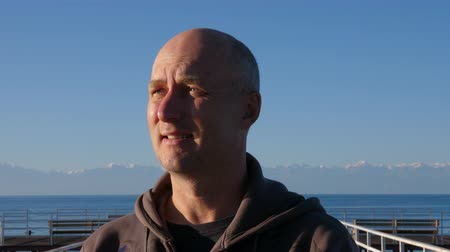 bald mountain : Alone man with sideward gaze on face, with lake and mountains on background Stock Footage