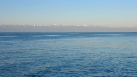 kul : Blue calm water in Issyk-Kul lake with mountains on background