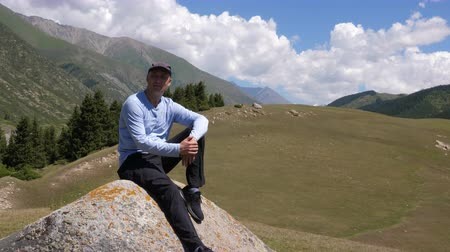 Альпы : Thoughtful man looking at sideway while resting on big stone in valley in mountains Стоковые видеозаписи