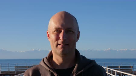bald mountain : Happy mature man smiling and looking at camera, with lake and mountains on background