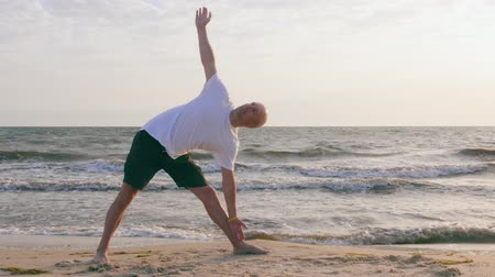 pozisyon : Athletic man practicing yoga in extended triangle asana on sea shore Stok Video