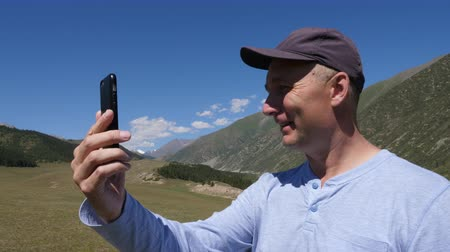 facetime : Smiling man in cap waving and having video chat on phone in Tian Shan mountains, Kyrgyzstan