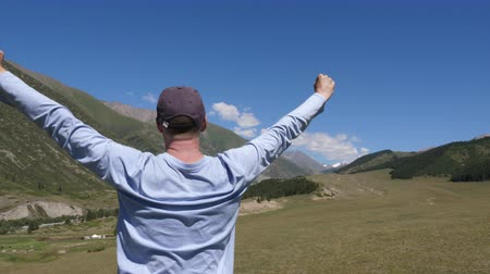 cheerfulness : Happy man standing and stretching hands up and enjoying life on mountain view