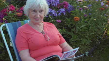 nagymama : Senior woman reading magazine in flower garden at summer day