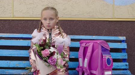 buket : Serious schoolgirl waiting on bench with flower bouquet and pink backpack Stok Video