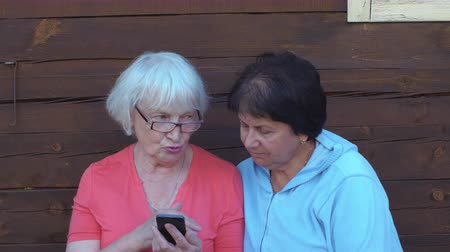 общаться : Two senior woman looking mobile phone and talking outdoor in countryside