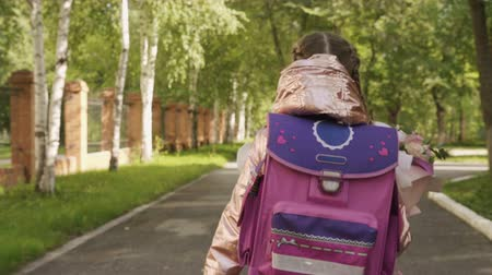 learning to walk : Little girl with backpack going to school with bouquet flowers. Back to school Stock Footage