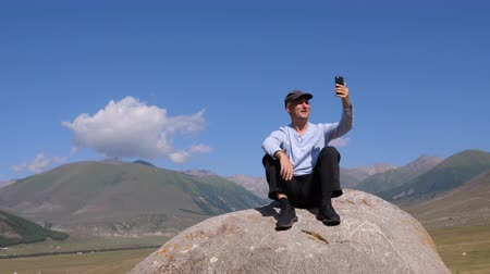 facetime : Cheerful man having video chat on phone while resting on stone in mountains