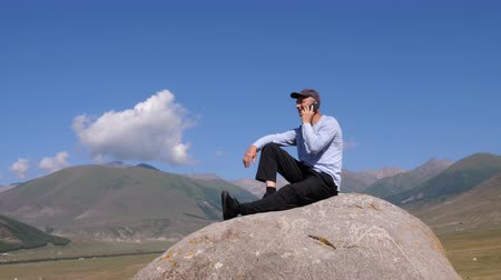 communion : Man calling by mobile phone sitting on big stone at mountain landscape