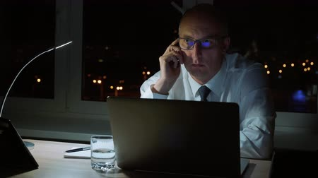 compromisso : Executive businessman talking to phone sitting at table in dark office at night Vídeos