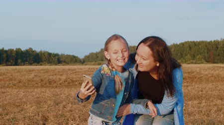 гаджет : Daughter kissing mom and making selfie photo to mobile phone on summer field