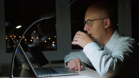 závazek : Adult businessman drinking water from glass and working by laptop in night office